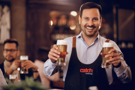 Young happy waiter holding two glasses of beer and looking at camera while working in a bar.